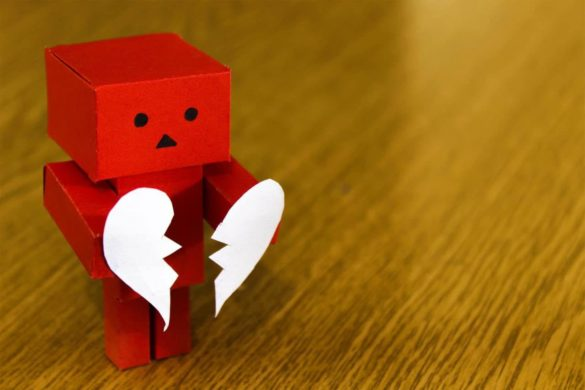 Sad robot holding a broken heart